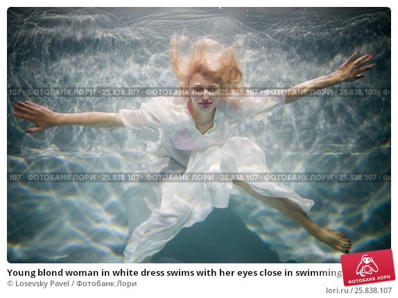 Купить «Young blond woman in white dress swims with her eyes close in swimming pool underwater», фото № 25838107, снято 14 мая 2016 г. (c) Losevsky Pavel / Фотобанк Лори