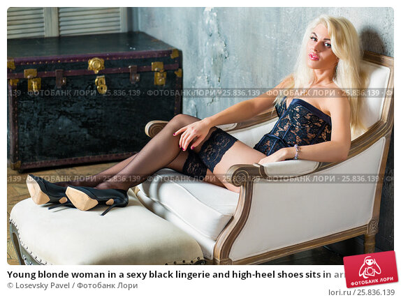 Купить «Young blonde woman in a sexy black lingerie and high-heel shoes sits in armchair with her feet on footrest in room», фото № 25836139, снято 17 сентября 2015 г. (c) Losevsky Pavel / Фотобанк Лори