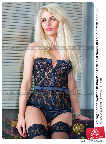 Купить «Young blonde woman in black lingerie and shoes sits on old-fashioned chest in room», фото № 25836091, снято 17 сентября 2015 г. (c) Losevsky Pavel / Фотобанк Лори