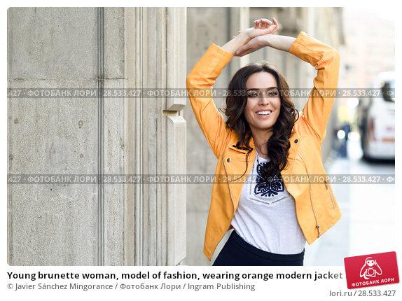 Купить «Young brunette woman, model of fashion, wearing orange modern jacket and blue skirt. Pretty caucasian girl with long wavy hairstyle smiling. Female raising her arms in urban background.», фото № 28533427, снято 11 марта 2017 г. (c) Ingram Publishing / Фотобанк Лори