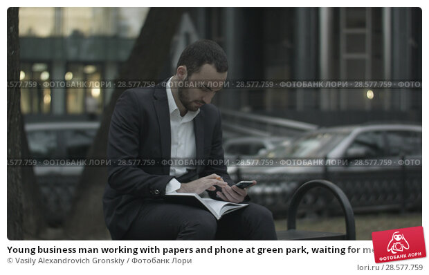 Купить «Young business man working with papers and phone at green park, waiting for meeting,», фото № 28577759, снято 19 июня 2018 г. (c) Vasily Alexandrovich Gronskiy / Фотобанк Лори