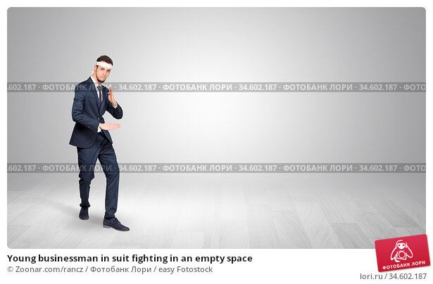 Young businessman in suit fighting in an empty space. Стоковое фото, фотограф Zoonar.com/rancz / easy Fotostock / Фотобанк Лори