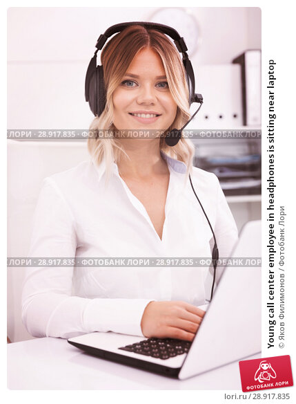 Купить «Young call center employee in headphones is sitting near laptop», фото № 28917835, снято 17 октября 2017 г. (c) Яков Филимонов / Фотобанк Лори