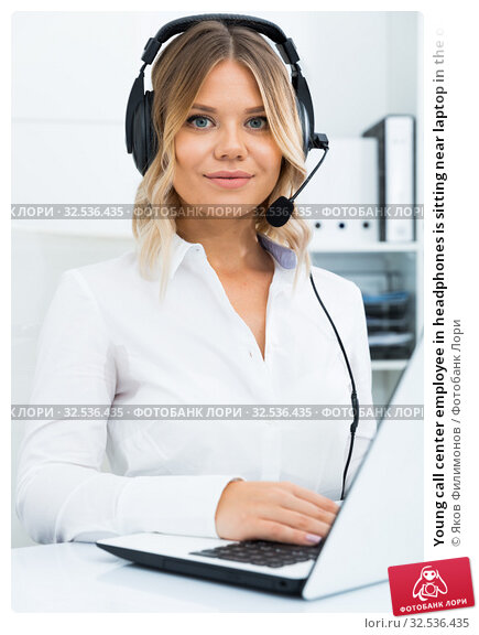 Купить «Young call center employee in headphones is sitting near laptop in the office», фото № 32536435, снято 17 октября 2017 г. (c) Яков Филимонов / Фотобанк Лори