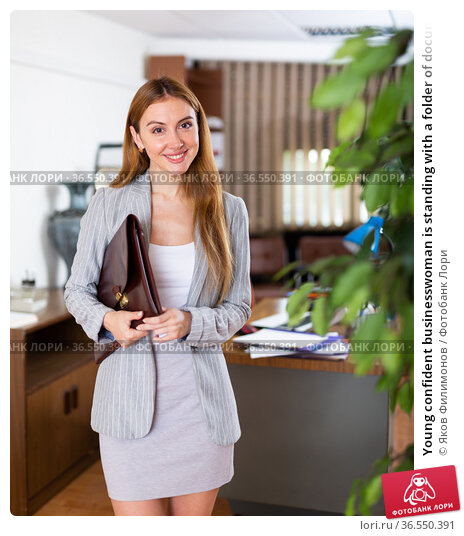 Young confident businesswoman is standing with a folder of documents in a office. Стоковое фото, фотограф Яков Филимонов / Фотобанк Лори