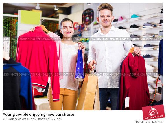 Купить «Young couple enjoying new purchases», фото № 30607135, снято 22 ноября 2016 г. (c) Яков Филимонов / Фотобанк Лори