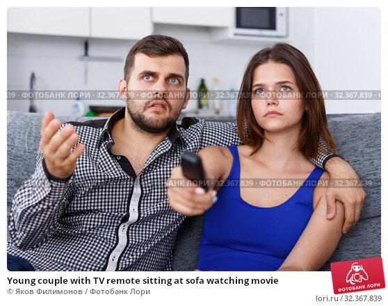 Young couple with TV remote sitting at sofa watching movie. Стоковое фото, фотограф Яков Филимонов / Фотобанк Лори