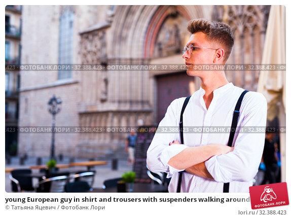 Купить «young European guy in shirt and trousers with suspenders walking around city», фото № 32388423, снято 27 июня 2018 г. (c) Татьяна Яцевич / Фотобанк Лори