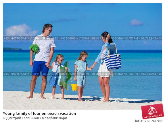 Купить «Young family of four on beach vacation», фото № 30761943, снято 4 апреля 2015 г. (c) Дмитрий Травников / Фотобанк Лори