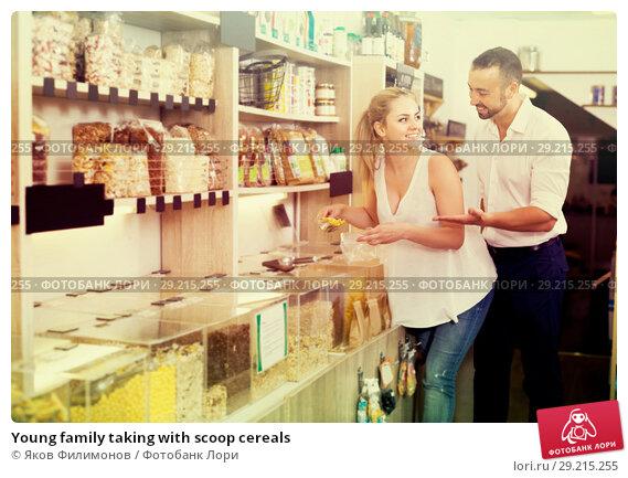 Купить «Young family taking with scoop cereals», фото № 29215255, снято 22 октября 2018 г. (c) Яков Филимонов / Фотобанк Лори