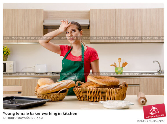 Young female baker working in kitchen. Стоковое фото, фотограф Elnur / Фотобанк Лори