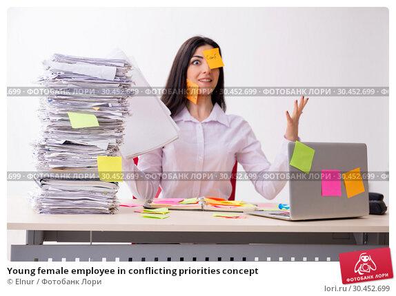 Young female employee in conflicting priorities concept. Стоковое фото, фотограф Elnur / Фотобанк Лори