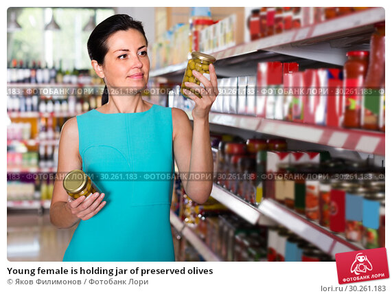 Купить «Young female is holding jar of preserved olives», фото № 30261183, снято 6 июня 2017 г. (c) Яков Филимонов / Фотобанк Лори