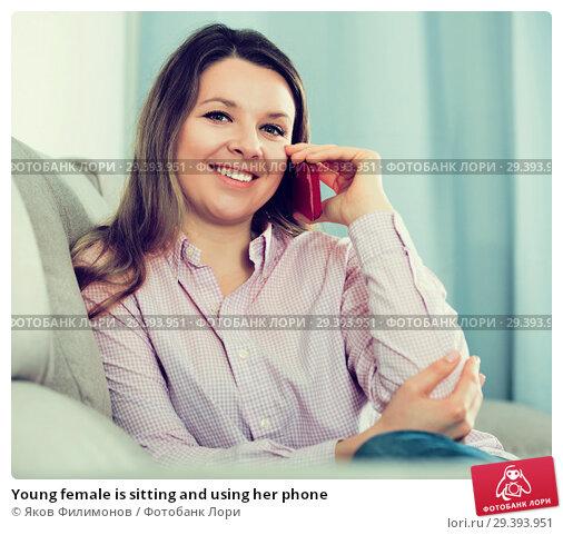Купить «Young female is sitting and using her phone», фото № 29393951, снято 13 марта 2017 г. (c) Яков Филимонов / Фотобанк Лори