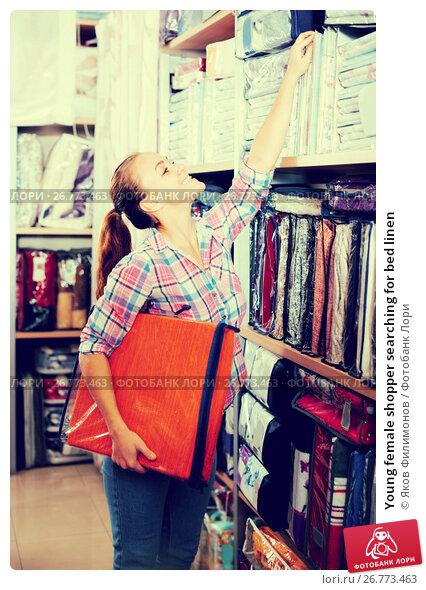 Купить «Young female shopper searching for bed linen», фото № 26773463, снято 25 мая 2018 г. (c) Яков Филимонов / Фотобанк Лори