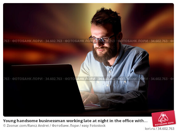 Young handsome businessman working late at night in the office with... Стоковое фото, фотограф Zoonar.com/Rancz Andrei / easy Fotostock / Фотобанк Лори