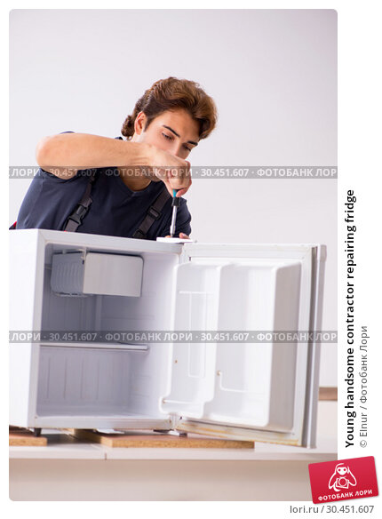 Young handsome contractor repairing fridge. Стоковое фото, фотограф Elnur / Фотобанк Лори