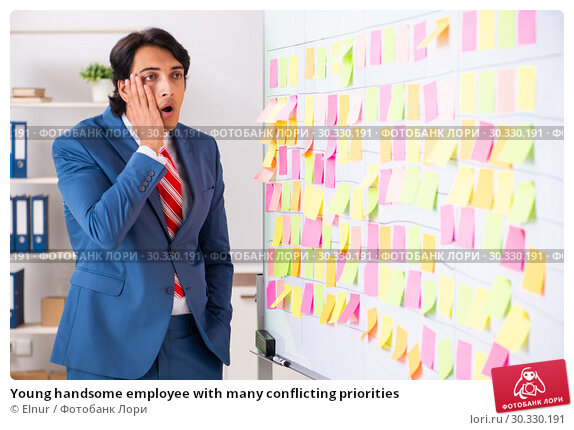 Купить «Young handsome employee with many conflicting priorities», фото № 30330191, снято 16 октября 2018 г. (c) Elnur / Фотобанк Лори