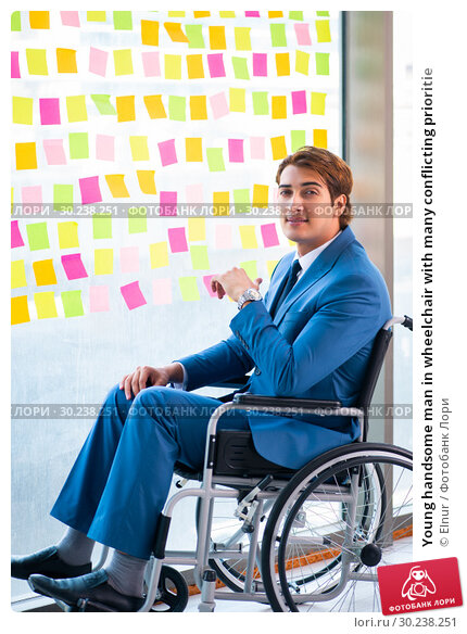 Купить «Young handsome man in wheelchair with many conflicting prioritie», фото № 30238251, снято 25 августа 2018 г. (c) Elnur / Фотобанк Лори