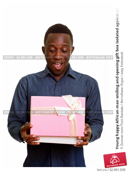 Young happy African man smiling and opening gift box isolated against white background. Стоковое фото, фотограф Zoonar.com/Toni Rantala / easy Fotostock / Фотобанк Лори