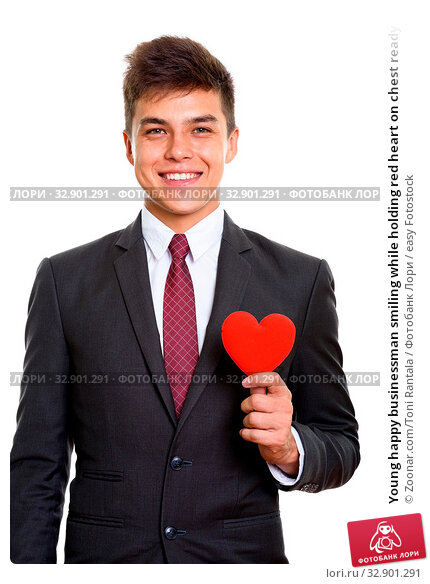 Young happy businessman smiling while holding red heart on chest ready for Valentine's day. Стоковое фото, фотограф Zoonar.com/Toni Rantala / easy Fotostock / Фотобанк Лори