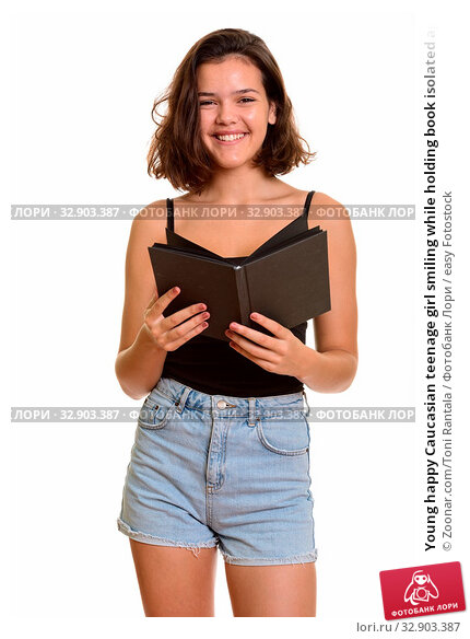Young happy Caucasian teenage girl smiling while holding book isolated against white background. Стоковое фото, фотограф Zoonar.com/Toni Rantala / easy Fotostock / Фотобанк Лори