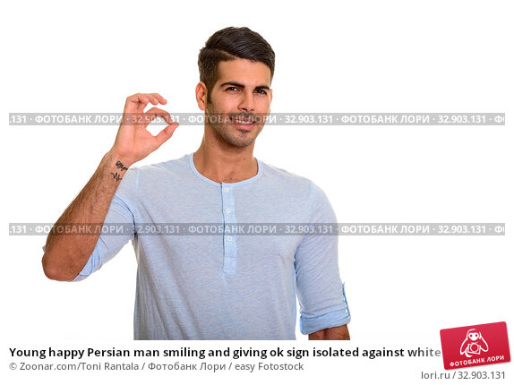Young happy Persian man smiling and giving ok sign isolated against white background. Стоковое фото, фотограф Zoonar.com/Toni Rantala / easy Fotostock / Фотобанк Лори