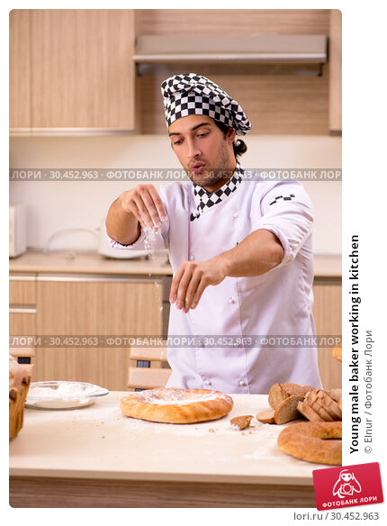 Young male baker working in kitchen. Стоковое фото, фотограф Elnur / Фотобанк Лори