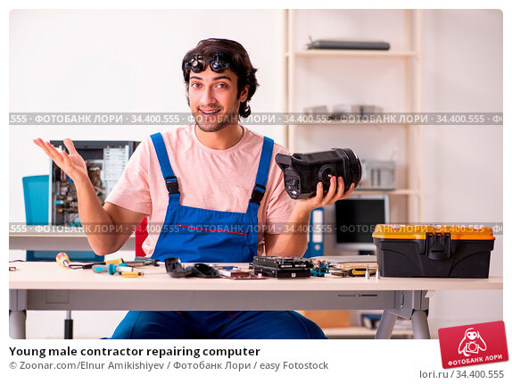 Young male contractor repairing computer. Стоковое фото, фотограф Zoonar.com/Elnur Amikishiyev / easy Fotostock / Фотобанк Лори