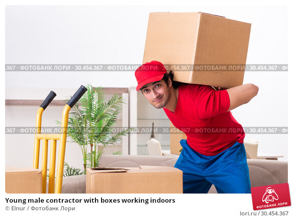 Young male contractor with boxes working indoors. Стоковое фото, фотограф Elnur / Фотобанк Лори