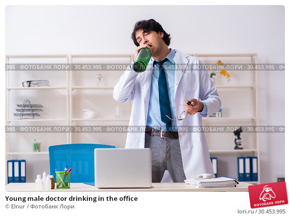 Young male doctor drinking in the office. Стоковое фото, фотограф Elnur / Фотобанк Лори