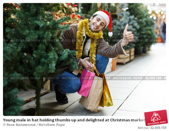 Young male in hat holding thumbs up and delighted at Christmas market. Стоковое фото, фотограф Яков Филимонов / Фотобанк Лори