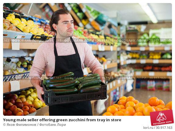 Купить «Young male seller offering green zucchini from tray in store», фото № 30917163, снято 27 апреля 2019 г. (c) Яков Филимонов / Фотобанк Лори