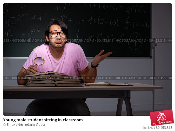 Young male student sitting in classroom. Стоковое фото, фотограф Elnur / Фотобанк Лори