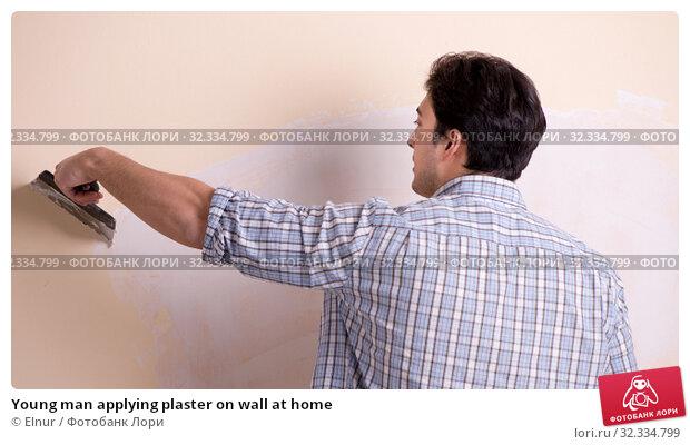 Купить «Young man applying plaster on wall at home», фото № 32334799, снято 15 марта 2018 г. (c) Elnur / Фотобанк Лори