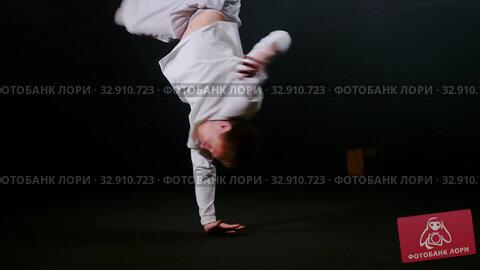 Young man dancer spinning aroung on one hand and keeping the balance. Стоковое видео, видеограф Константин Шишкин / Фотобанк Лори