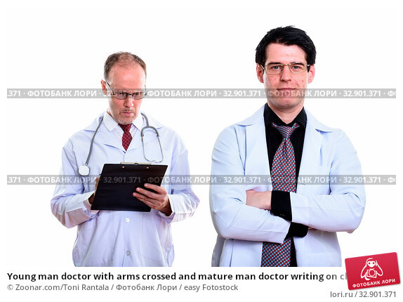 Young man doctor with arms crossed and mature man doctor writing on clipboard. Стоковое фото, фотограф Zoonar.com/Toni Rantala / easy Fotostock / Фотобанк Лори