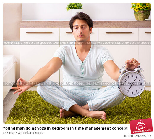 Young man doing yoga in bedroom in time management concept. Стоковое фото, фотограф Elnur / Фотобанк Лори