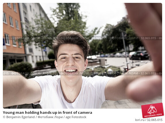 Young man holding hands up in front of camera. Стоковое фото, фотограф Benjamin Egerland / age Fotostock / Фотобанк Лори