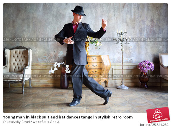 Купить «Young man in black suit and hat dances tango in stylish retro room», фото № 25841259, снято 4 июня 2015 г. (c) Losevsky Pavel / Фотобанк Лори