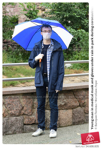 Young man in medical mask and gloves under rain in park during coronavirus pandemic (covid-19) Стоковое фото, фотограф Валерия Попова / Фотобанк Лори