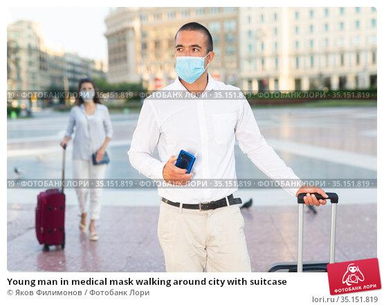 Young man in medical mask walking around city with suitcase. Стоковое фото, фотограф Яков Филимонов / Фотобанк Лори