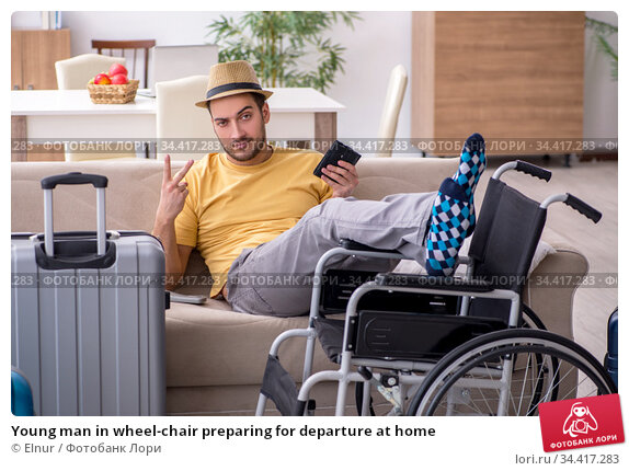 Young man in wheel-chair preparing for departure at home. Стоковое фото, фотограф Elnur / Фотобанк Лори