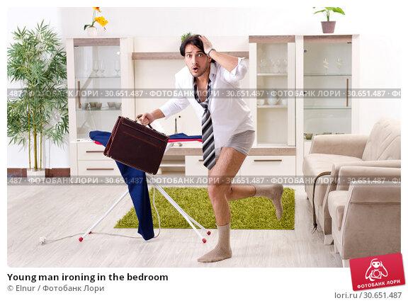 Купить «Young man ironing in the bedroom», фото № 30651487, снято 29 ноября 2018 г. (c) Elnur / Фотобанк Лори