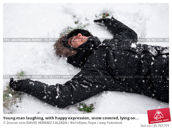 Young man laughing, with happy expression, snow covered, lying on... Стоковое фото, фотограф Zoonar.com/DAVID HERRAEZ CALZADA / easy Fotostock / Фотобанк Лори