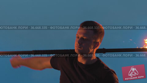 Young man performer in black clothes playing with fire at night. Стоковое видео, видеограф Константин Шишкин / Фотобанк Лори