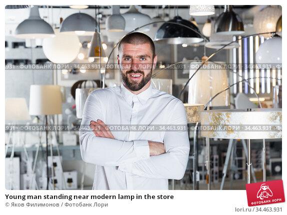 Young man standing near modern lamp in the store. Стоковое фото, фотограф Яков Филимонов / Фотобанк Лори