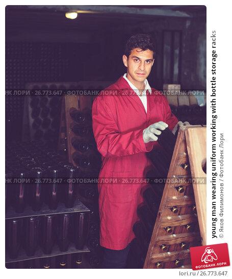 Купить «young man wearing uniform working with bottle storage racks», фото № 26773647, снято 21 сентября 2016 г. (c) Яков Филимонов / Фотобанк Лори