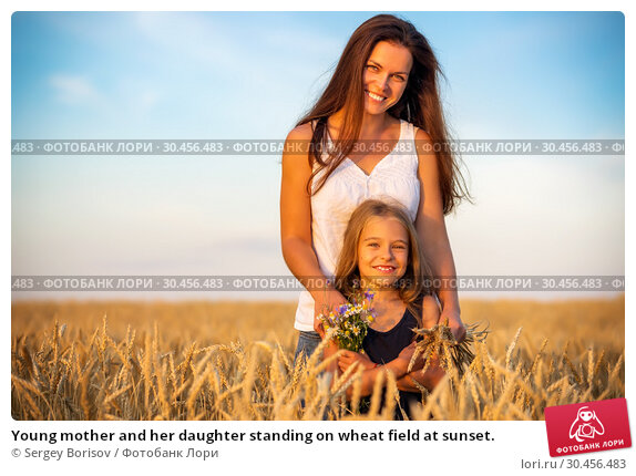 Young mother and her daughter standing on wheat field at sunset. Стоковое фото, фотограф Sergey Borisov / Фотобанк Лори