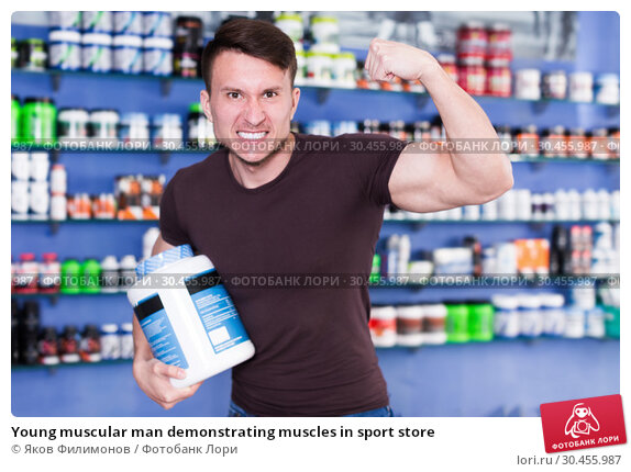 Young muscular man demonstrating muscles in sport store. Стоковое фото, фотограф Яков Филимонов / Фотобанк Лори